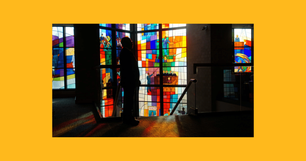 Henry Louis Gates silhouetted before stained glass window at Trinity UCC, Chicago