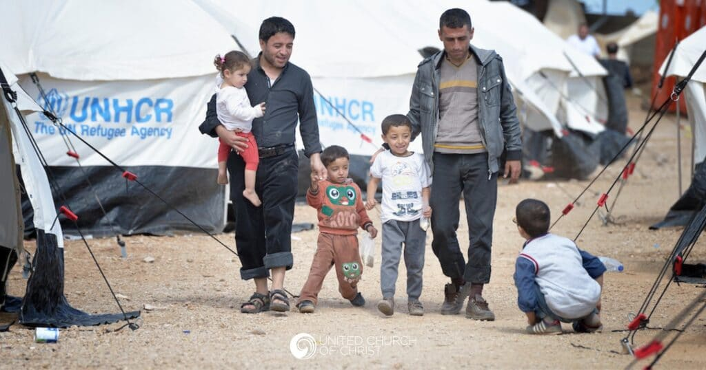 Refugee family by UNHCR tent