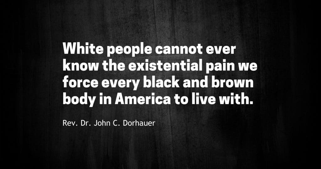 """Dark image with the words, """"White people cannot ever know the existential pain we force every black and brown body in America to live with. -Rev. Dr. John C. Dorhauer."""""""