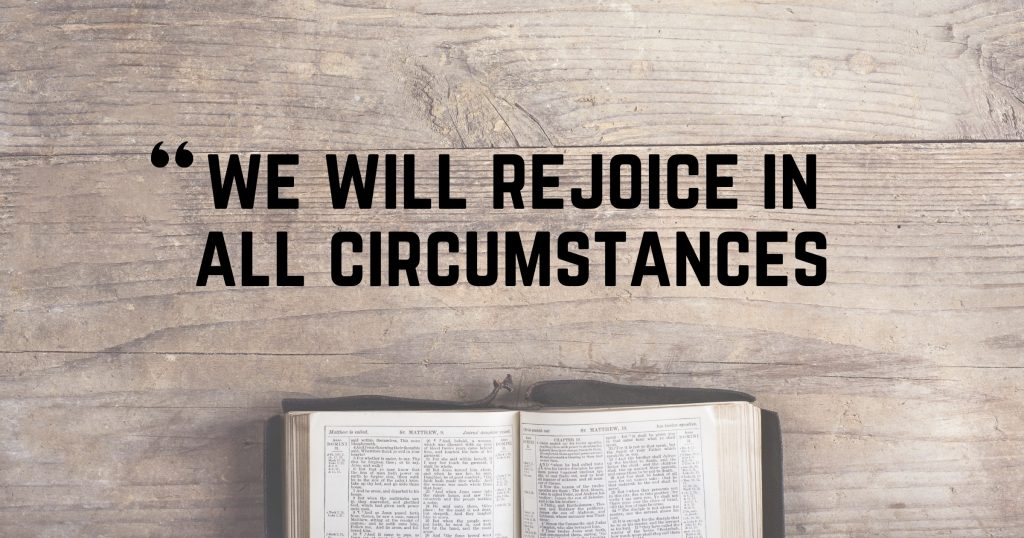 """Picture of an open Bible on a wood table with the words, """"We will rejoice in all circumstances"""""""