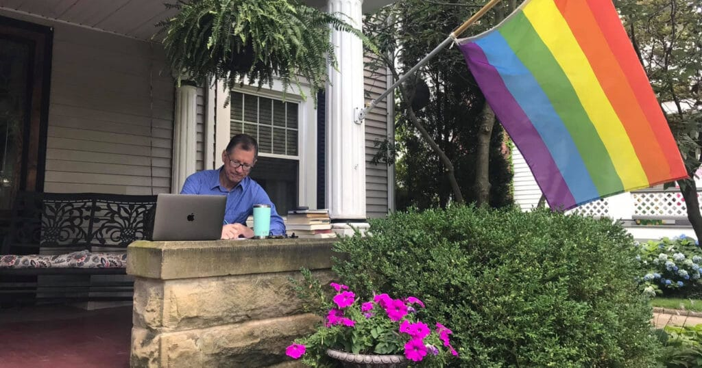 Picture of Rev. Dr. John C. Dorhauer sitting on his porch, writing in a notebook. His laptop, a stack of books, and a coffee cup are nearby. There are many plants, flowers, a bench, and a LGBTQ+ Pride flag around the space.