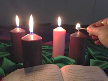 4 Advent candles on green cloth with a Bible in the foreground. From left to rights: 2 lit purple candles, 1 lit pink candle and a person lighting the far right purple candle with a match.